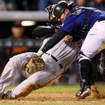 Colorado Rockies catcher Michael McKenry, front, tags out San Francisco Giants' Casey McGehee as he tries to score on a single by Nori Aoki during the fifth inning of the second game of a baseball doubleheader Saturday, May 23, 2015, in Denver. (AP Photo/David Zalubowski)