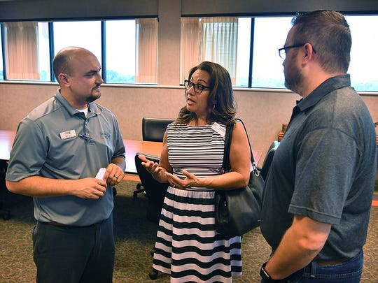 Matt Yell, left, president and CEO of the North Texas Area United Way, and board president David Cook visit with Toni Alonzo, executive director of Communities In Schools, at a luncheon Thursday at Wells Fargo Bank.