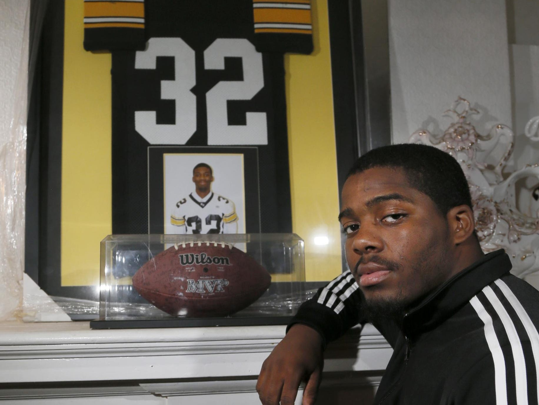 Detroit King senior running back Martell Pettaway poses with the framed jersey, photo and football from older brother, Devinne, who played for King and passed away in 2008. Pettaway wears the same No. 32.