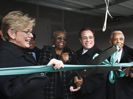 Sallie Sanders, second from left, is helped by then Michigan Gov. Jennifer Granholm, left, former Wayne County Executive Robert Ficano and Judge Damon Keith with a ribbon cutting outside her new house in Hamtramck on Jan. 18. 2010.