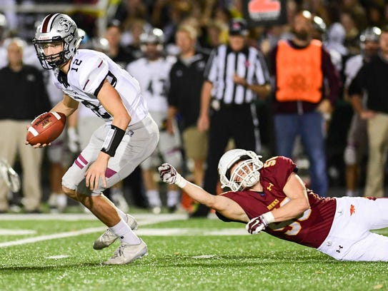 Ankeny's Luke Sable (56) tries to hang on to sack Ankeny