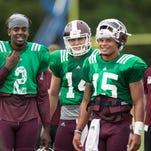 Mississippi State quarterbacks Elijah Staley (2) and Nick Tiano (14) talk with Dak Prescott during practice earlier this month.