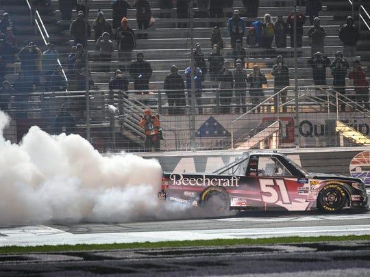 Kyle Busch does a burnout after winning the NASCAR Truck Series auto race at Atlanta Motor Speedway, Saturday, Feb. 23, 2019, in Hampton, Ga. (AP Photo/John Amis)