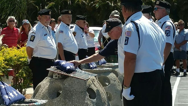 Theodore Robbins, who served in the South Pacific during World War II, lays a flag on a memorial reef in honor of six B-26 bomber airmen who died during a training exercise off the coast of Fort Myers Beach.