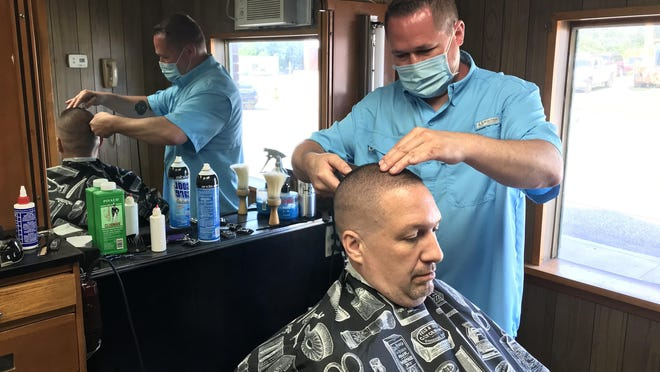 Nick Garver, 42, cuts Ed Brink's hair Tuesday at Garver's Barbers & More, 1801 W. 26th St. Garver decided to open his shop despite the fact that Erie County remains in the yellow phase of the state's COVID-19 reopening plan.