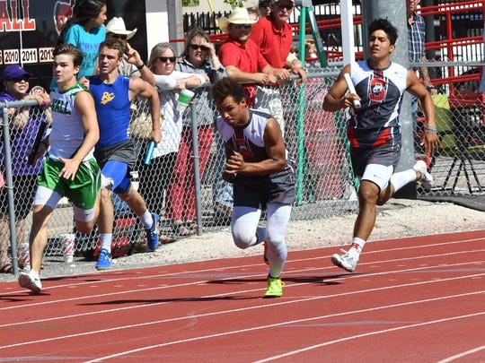 Sonora's Willie Munoz hands off to Jarrett Jackson at the Districts 3/4-3A Area Meet April 20 in Sonora.