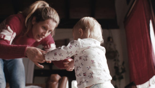 "A mother helps a baby girl take her first steps in the 2-minute ""Pick Them Back Up"" video for the Sochi Olympics."