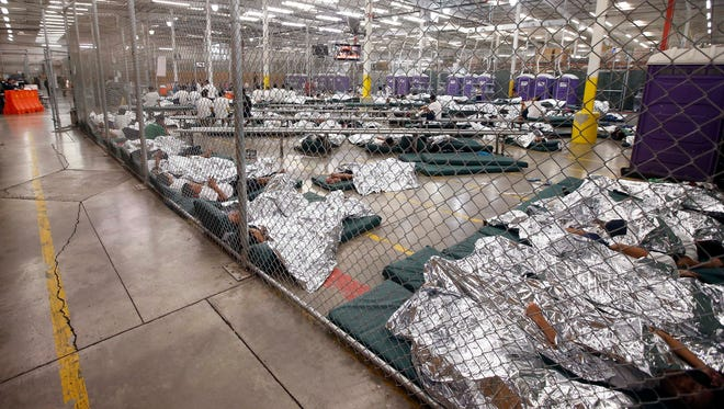 Detainees sleep and watch television June 18, 2014, in a holding cell where hundreds of mostly Central American immigrant children are being processed and held at the U.S. Customs and Border Protection placement center in Nogales, Ariz.
