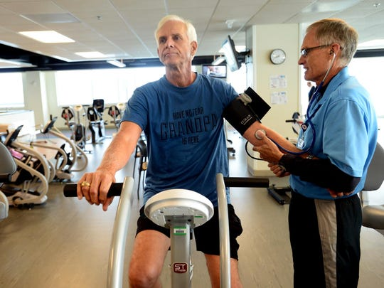 Douglas Clark, left, who recently suffered a heart attack, has his blood pressure taken by Bon Secours St. Francis Cardio Pulminary Rehab senior exercise specialist Roy Kulikowski as Clark works out in the HealThy self gym in Greenville, S.C.