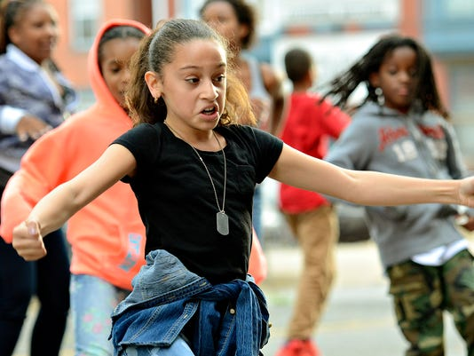 Sanicia Castro, 8, of Seven Valleys, and others dance in the street as music plays during Mardi Gras Noir Picnic Cook Off & Chopped Competition block party at G's Jook Joint Restaurant & Lounge in York, Pa. on Saturday, Sept. 26, 2015. Dawn J. Sagert - dsagert@yorkdispatch.com