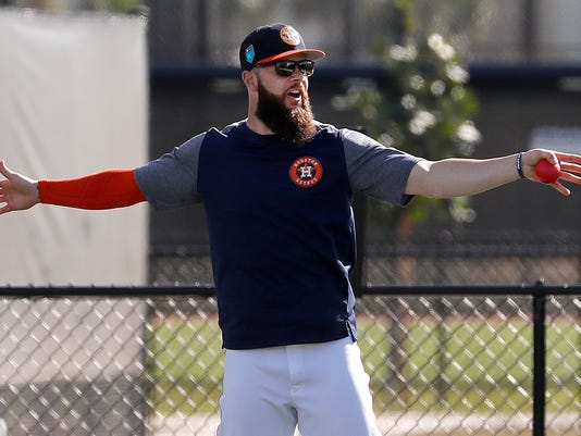 FILE - In this Feb. 15, 2018, file photo, Houston Astros pitcher Dallas Keuchel stretches during spring training baseball practice in West Palm Beach, Fla. After bouncing back from a disappointing 2016 to help the Houston Astros win their first World Series last season Dallas Keuchel is eager to do more this year to help the Astros replicate their success. (AP Photo/Jeff Roberson, File)