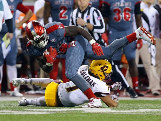 Miami RedHawks running back Alonzo Smith (26) is tackled
