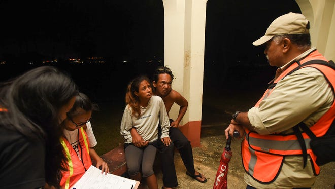Guam Homeless Coalition member Kat Uchima, right, speaks with Anthony Lizama, 46, and Marina Roberto, 42, during a survey at Paseo de Susana Park in Hagåtña on Jan. 26, 2018.