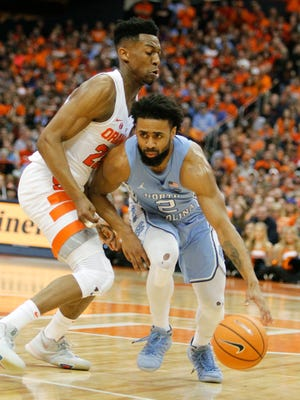 North Carolina's Joel Berry II, right, dribbles past Syracuse's Tyus Battle, left, during the first half of an NCAA college basketball game in Syracuse, N.Y., Wednesday, Feb. 21, 2018. (AP Photo/Nick Lisi)