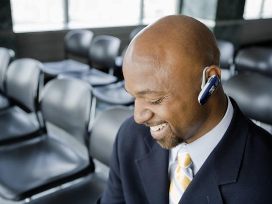 A businessman wearing a wireless headset.