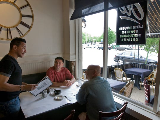 Rico Rivera, owner of Bistro Olé, talks with customers Shamil Tairov and Jay Bernstein in this 2010 file photo. The restaurant is one of several in Asbury Park that has closed in recent months.