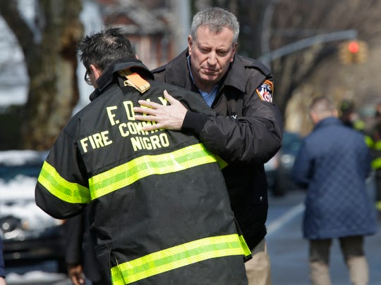 New York City Mayor Bill de Blasio hugs Fire Commissioner Daniel Nigro as he arrives at the scene of a fatal fire in the Brooklyn borough of New York, Saturday, March 21, 2015. The fire raged through a residence early Saturday, killing seven children and leaving two other people in critical condition, authorities said. (AP Photo/Mary Altaffer)