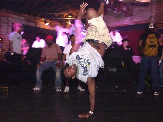 "July 23, 2003: Darrick Johnson break-dances while MC Clifford Joseph Jonhson, i.e. ""C2J,"" performs at Top Cats."