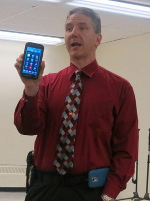Detective Edward de la Fuente holds up his mobile phone while speaking to a group of parents about the dangers of children using several new cell phone applications during a forum at the Millburn Free Public Library March 14, 2016.