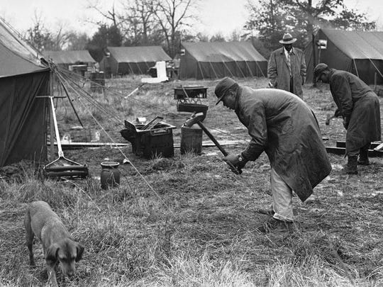Two African-American men drive the final stakes into the ground after putting up a new tent at Tent City, which was built for evicted tenant farmers in Fayette County,  Tenn., on Dec. 30, 1960. African Americans taking up residence in the tents claim the evictions were ordered in retaliation against those who registered to vote.