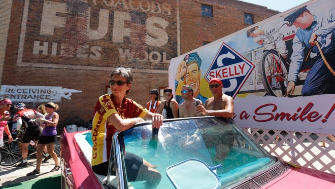 Carolyn Stanek of Hindsdale, Ill. (left), watches the band play as a group of riders cool off in the back of a car converted into a pool Tuesday, July 26, 2016, during the third day of RAGBRAI from Creston to Leon.