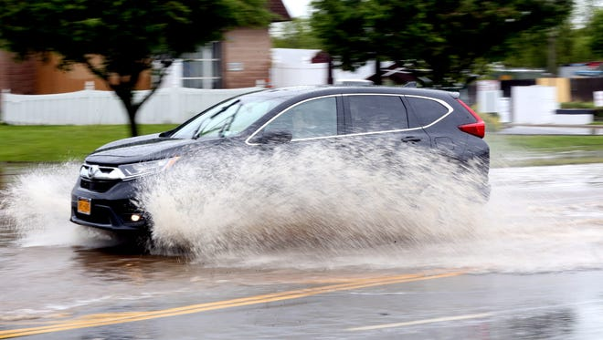 Cars navigate the flood waters on Route 59 near Palisade Center in West Nyack May 5, 2017.
