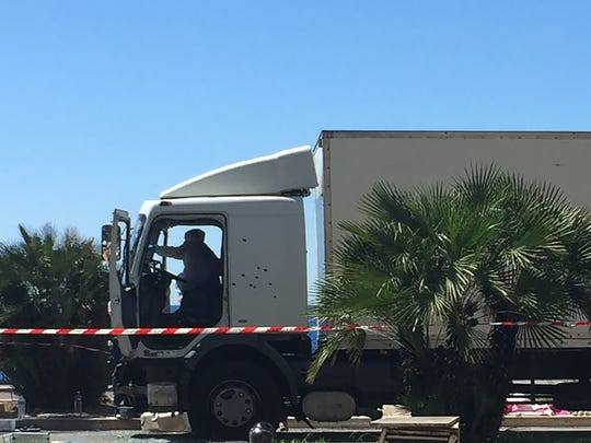 This picture taken on July 15, 2016, with a mobile phone, shows forensics officers and policemen looking for evidence near a truck on the Promenade des Anglais seafront in the French Riviera town of Nice, after it drove into a crowd watching a fireworks display.