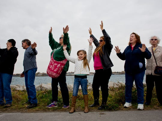 Karina Martinez, 8, of Port Huron, holds up her hands and dances along with dozens of others during a promotional video shoot Saturday on the Blue Water River Walk in Port Huron.