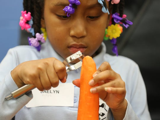 Jaelyn Phillips, 7, peels a carrot in a family cooking class at Born Learning Academy in John P. Parker School.