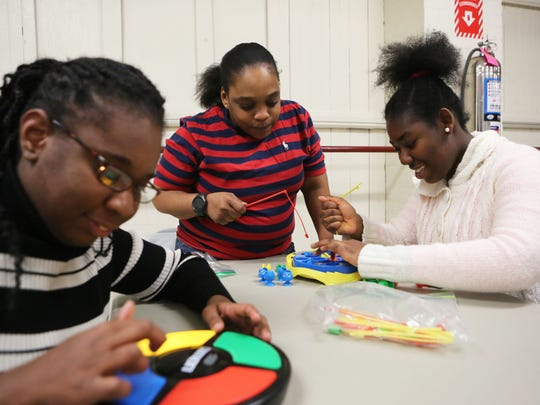Abbigay Johnson, 19, right, plays a fishing game with staffer Suzette Swain as Zyhedy Pinnock, 17, plays a memory game during the Rose Simon after-school program for developmentally disabled youths at the Mount Vernon Armory, March 22, 2017.