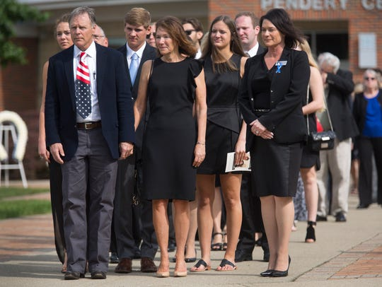 Fred and Cindy Warmbier watch as pallbearers carry