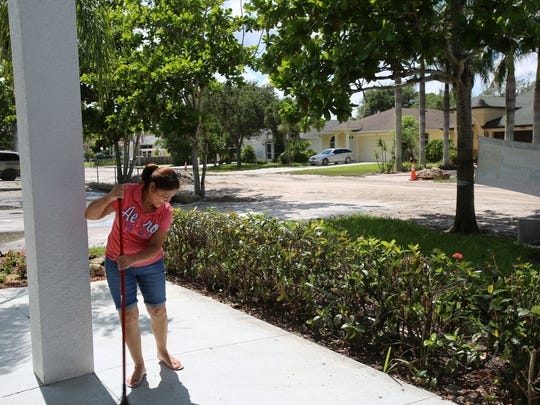 Martha Lizardo, a member of the congregation at Iglesia Pentecostes Peniel in North Naples, sweeps up outside Wednesday, July 12, 2017.
