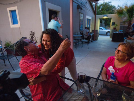 Xóchitl Torres Small, center, hugs Fidel Sanchez, left, as he and his wife Rosemarie Sanchez, right,  congratulate her for winning the democratic nomination for Congressional District Two, Tuesday June 5, 2018, at Amaro Winery.