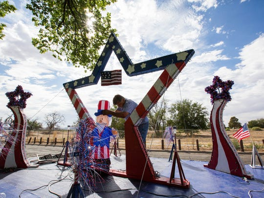 Rudy Romero turns on a generator and helps an inflatable Uncle Sam to stand upright in a demonstration of what the Las Cruces High School Class of 1971's float for the 2018 Electric Light Parade will look like, Tuesday July 3, 2018 at Apodaca Park. The Class of '71's float was constructed in three days, all from scrap material. The team was putting the final touches on the float at 11:30 p.m. Monday, Romero said.