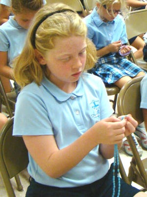 Riley Eberhard in Ann Mackenzie's second-grade class prays the rosary during the prayer service for peace at St. Joseph, Cold Spring. Behind her are Emma Orth and Melissa Geiman.