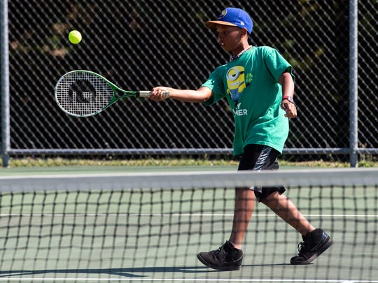 Landon Williams, 11, returns a hit during a practice drill on Wednesday, July 18, 2018. Around 67 kids, ranging from 7 to 16, participated in the free tennis program, teaching basic skills of the game.