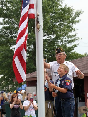 Nathan Beck helps the scouts with the flag-raising ceremony at the Belle Plaine July 4 celebration.