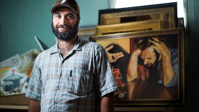 """Endwell artist Anthony Hanakovic, 37, with his piece """"The Calling of St. Matthews."""""""