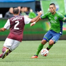 Aug 30, 2014; Seattle, WA, USA; Seattle Sounders FC forward Clint Dempsey (2) dribbles the ball past Colorado Rapids midfielder Nick LaBrocca (2) during the first half at CenturyLink Field. Seattle defeated Colorado 1-0. Mandatory Credit: Steven Bisig-USA TODAY Sports