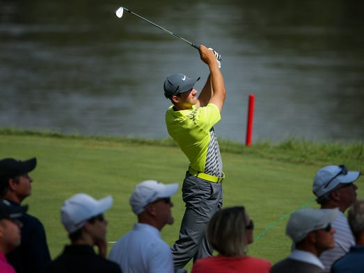Patrick Rodgers watches the flight of his 16th hole tee shot as the crowd looks on during the opening round of the John Deere Classic at TPC Deere Run, Thursday, July 10, 2014, in Silvis, Illinois.