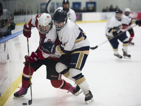 Players from CVU and Essex collide along the boards