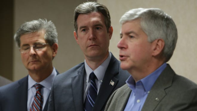 Flint Mayor Dayne Walling, center, listens as Gov. Rick Snyder speaks to the media during a news conference Thursday regarding the city of Flint switching back to the Detroit water system.