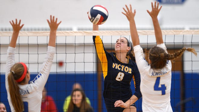 Victor's Amanda Dake, center, hits between the block of Webster Schroeder's Leigha Kircher (4) and Emma Draper during a regular-season game Monday at Schroeder. Victor won in three sets.