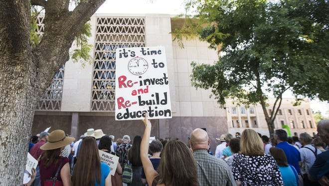 """Lisa Olson, a Mesa teacher and mother of five, holds up a sign during a """"Now it Starts"""" rally outside the State Capitol on May 19, 2016 in Phoenix, Ariz. The rally is to put pressure on leaders to focus on education funding no matter how the vote on Prop 123 turns out."""