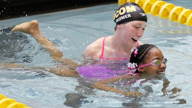 Grace Baumer of the Golden Comets swim team, left, helps Tyona Taver learn to swim in the pool at Monroe Community College as part of the program Successfully Transitioning Youth to Adolescence for city youth.