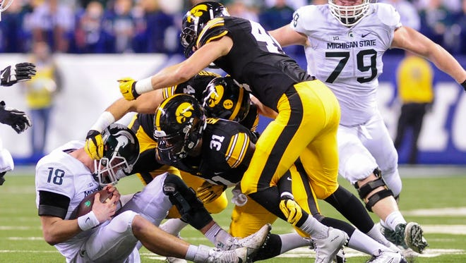 """Michigan State quarterback Connor Cook succombs to Iowa's """"Raider"""" package in the Big Ten title game as linebackers Aaron Mends (31), Bo Bower and Ben Niemann sack him in the Dec. 5 game in Indianapolis. Stanford quarterback Kevin Hogan thinks the Cardinal will be able to handle Iowa's third-down defense."""