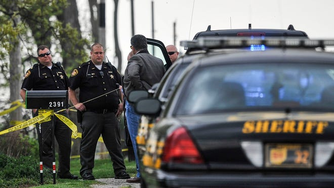 Marion County Sheriff's Office deputies and detectives converse on Pleasant Hill Road, where a gunshot victim's body was found on April 27.