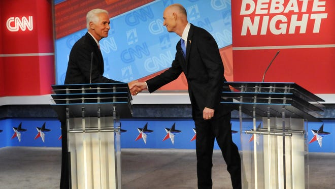 Democratic candidate Charlie Crist, left, and Republican Gov. Rick Scott shake hands before their live television debate, Tuesday, Oct. 21, 2014 hosted by WJXT-TV and CNN at the Channel 4 studios in Jacksonville, Fla. (AP Photo/The Florida Times-Union, Will Dickey, Pool) ORG XMIT: FLJAJ101