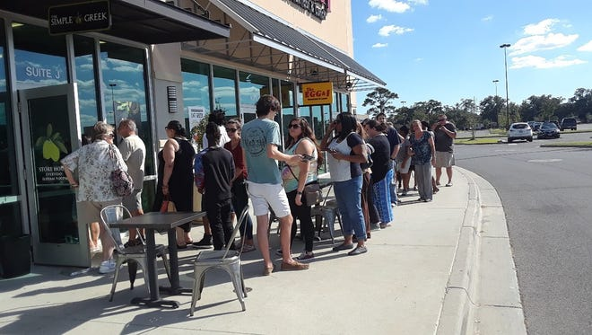 Customers wait in line to get into The Simple Greek restaurant.