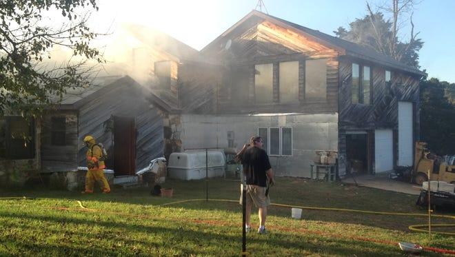 Firefighters work the scene of a residential blaze at 2838 Baxter County Road 46 near Henderson on Saturday afternoon.